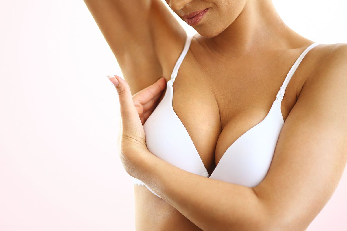 Woman With Breast Implants Conducts Self Breast Cancer Exam